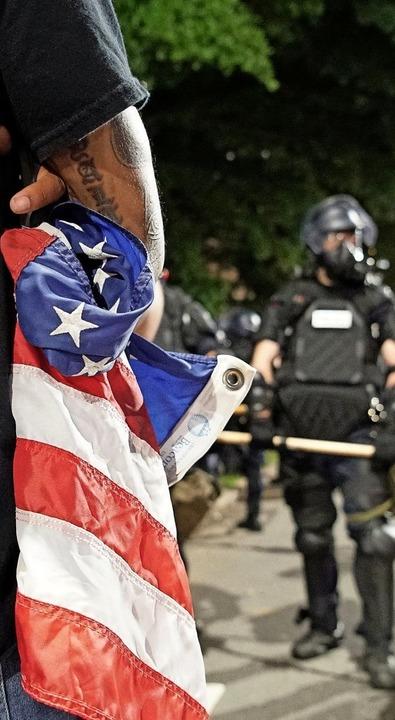 Ein Demonstrant hält eine zerfledderte...hm  gegenüber stehen Polizisten Wache.    Foto: Allen G. Breed (dpa)