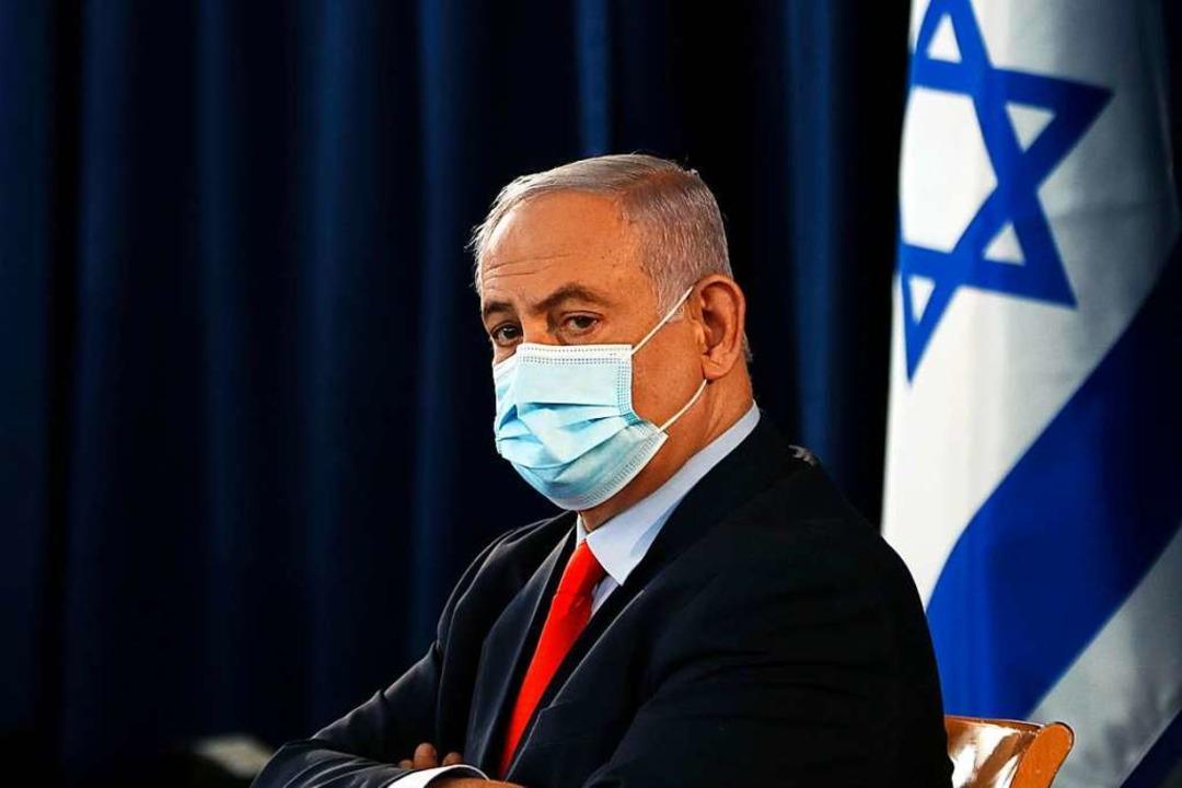 Der israelische Premier Benjamin Netan...entlichen Kabinettssitzung eine Maske.  | Foto: Ronen Zvulun (dpa)