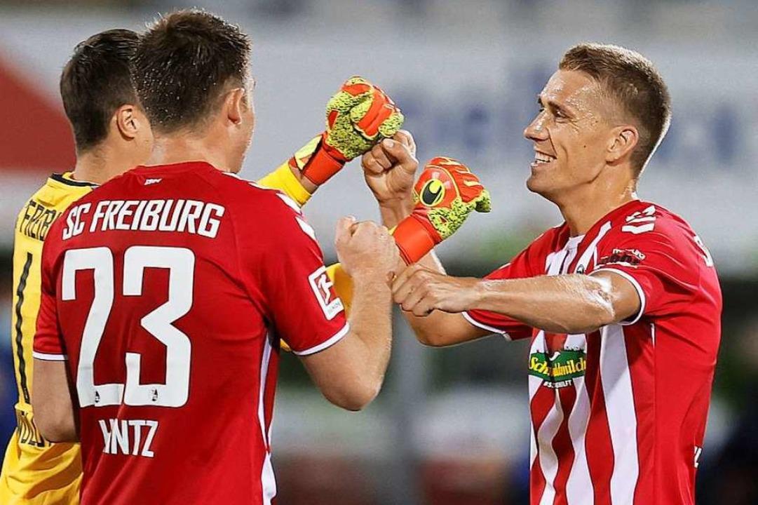 Nils Petersen (rechts) freut sich mit ...wart Alexander Schwolow über den Sieg.  | Foto: RONALD WITTEK (AFP)