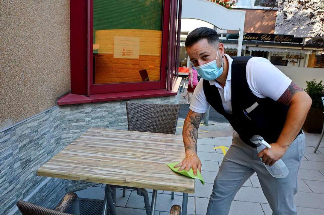 Salvatore Alu vom Restaurant da Giacomo desinfiziert einen Tisch.  | Foto: Horatio Gollin