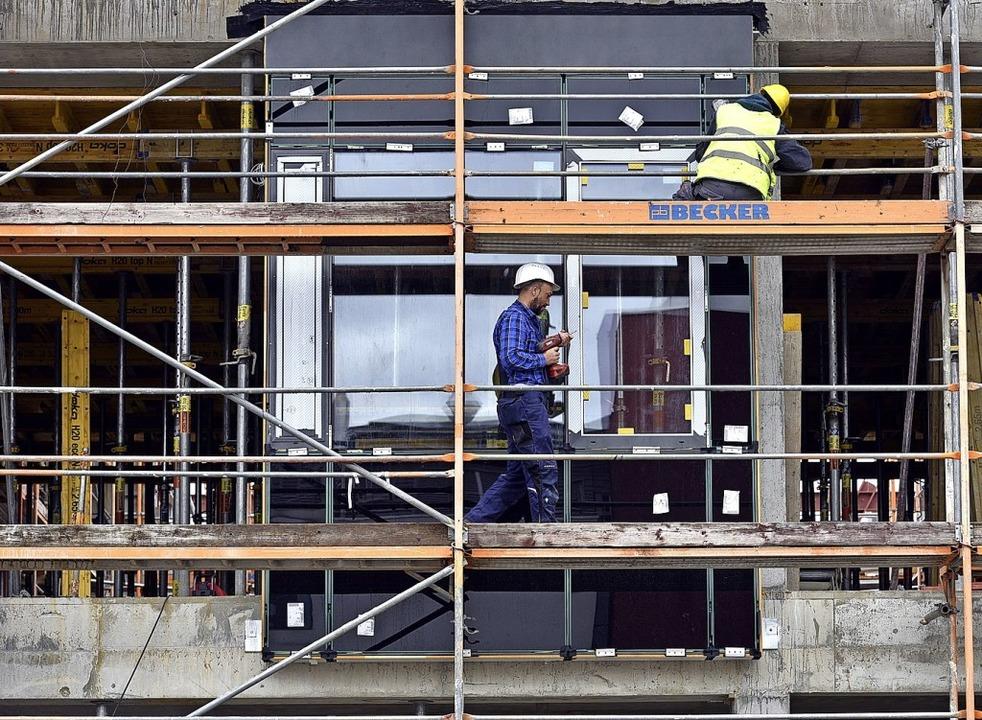 Während noch der Rohbau läuft, montier...rbeiter schon die erste Musterfassade.  | Foto: Thomas Kunz