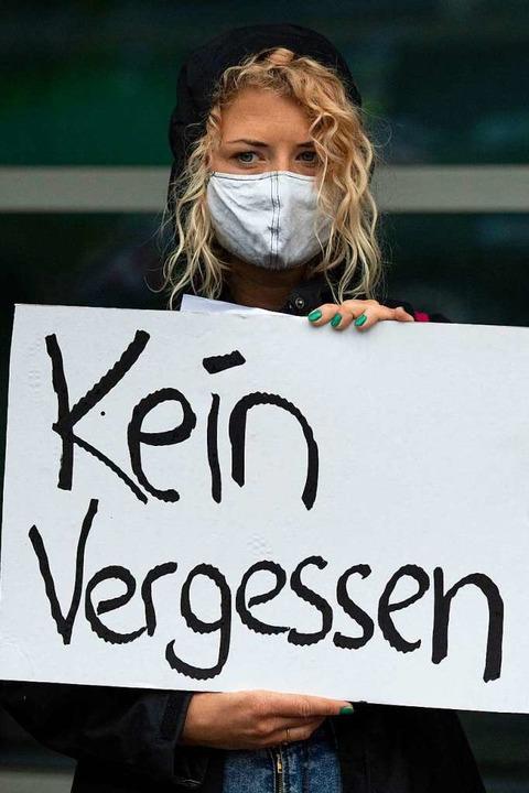 Demonstrantin vor dem Gerichtsgebäude  | Foto: Boris Roessler (dpa)