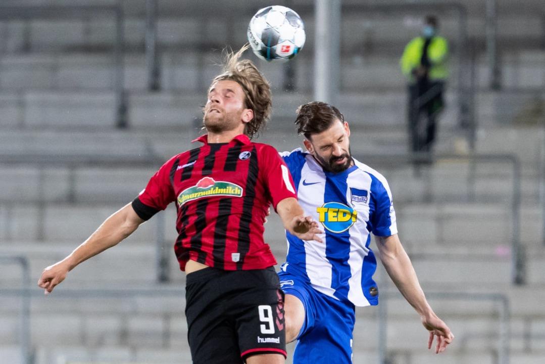 Lucas Höler im Luftzweikampf mit Marvin Plattenhardt.  | Foto: Tom Weller (dpa)