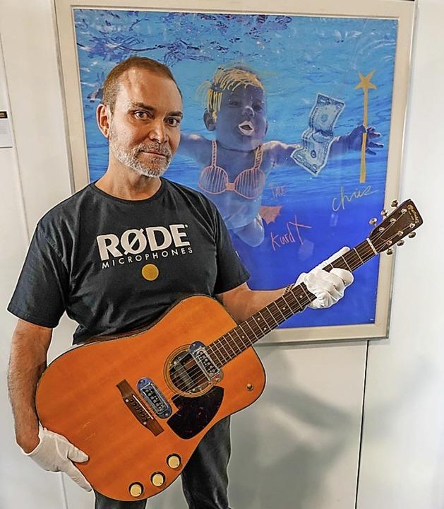 Peter Freedman mit  Rekord-Gitarre  | Foto: Julien's Auctions (dpa)