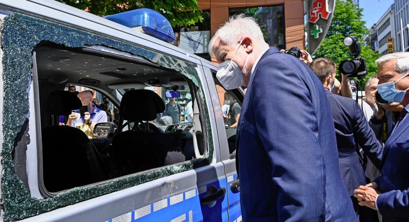 Ortstermin in Stuttgart: Bundesinnenmi...auptstadt ein demoliertes Polizeiauto.    Foto: THOMAS KIENZLE (AFP)