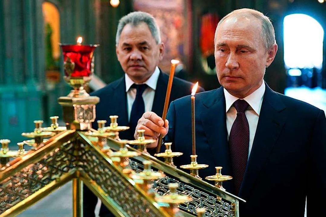 Wladimir Putin  zündet nach einem Gott...er Nazis in die Sowjetunion Kerzen an.  | Foto: Alexei Nikolsky (dpa)