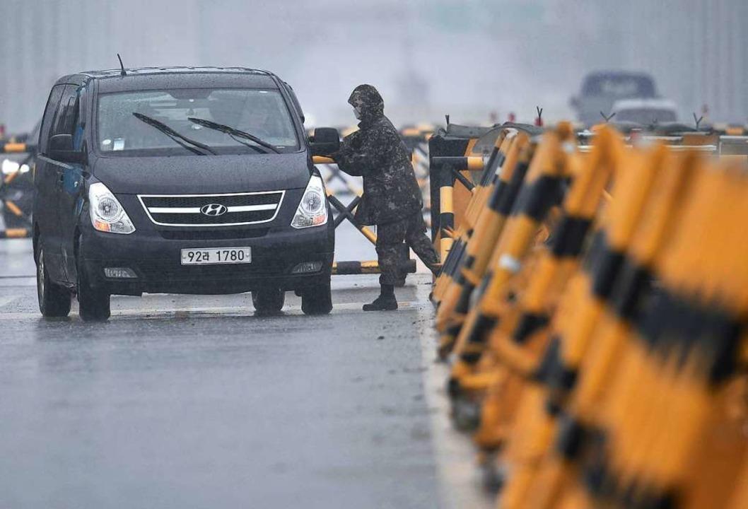 Ein südkoreanischer Soldat kontrolliert ein Fahrzeug an einem Checkpoint.  | Foto: JUNG YEON-JE (AFP)