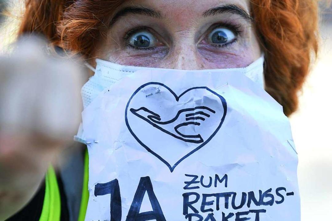 Diese Flugbegleiterin wirbt vor der Lu...le für die Annahme des Rettungspakets.  | Foto: Arne Dedert (dpa)