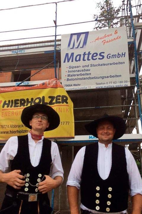 Die  Zimmerleute Max Schneider und Tho...fürs Richtfest auf dem Dach befestigt.    Foto: Annemarie Rösch