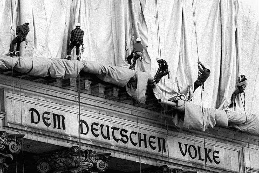 Eine Seilschaft rollt die Verhüllungsplanen für den Berliner Reichstag ab.  | Foto: Wolfgang Kumm (dpa)