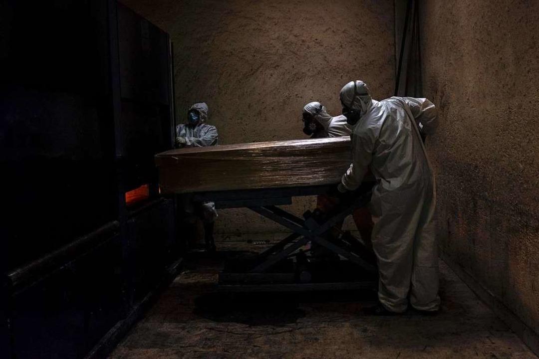 Mitarbeiter eines Krematoriums in Mexi...t tragen in Schutzanzügen  einen Sarg.  | Foto: Jacky Muniello (dpa)