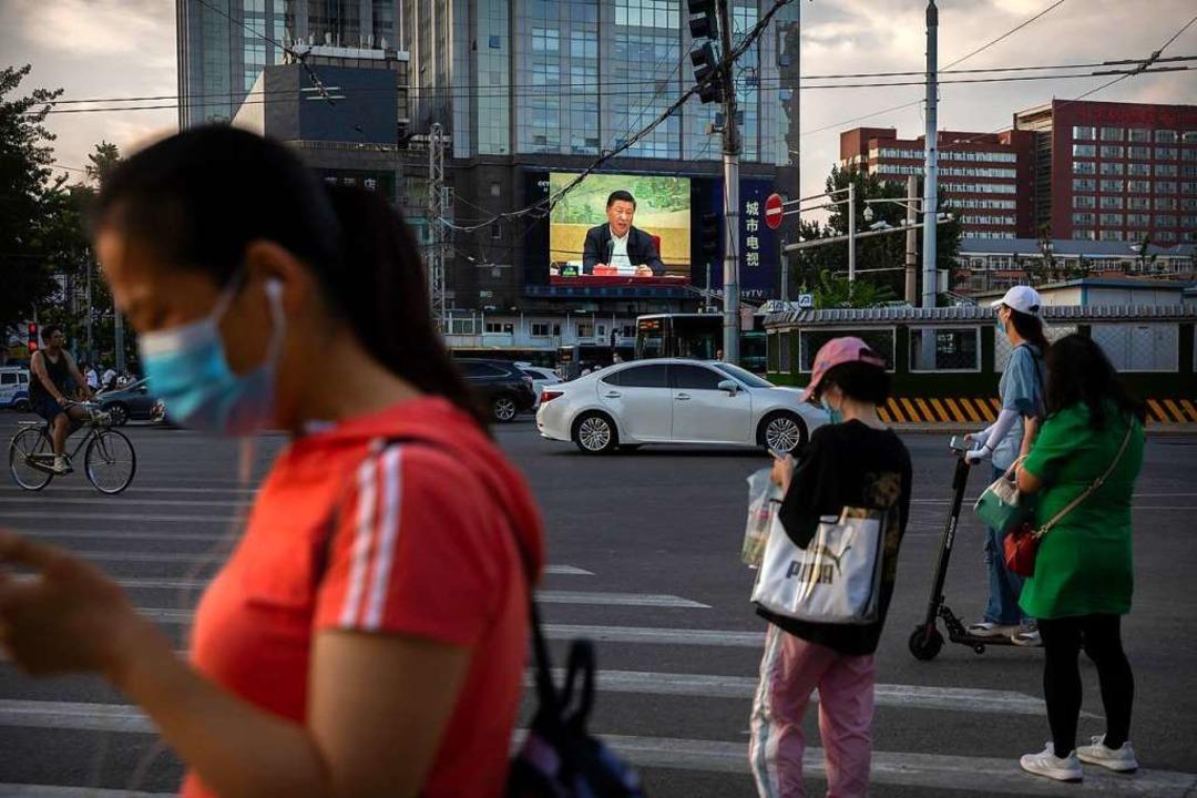 Passanten warten darauf, eine Kreuzung...nalen Sicherheit in Hongkong erlassen.  | Foto: Mark Schiefelbein (dpa)
