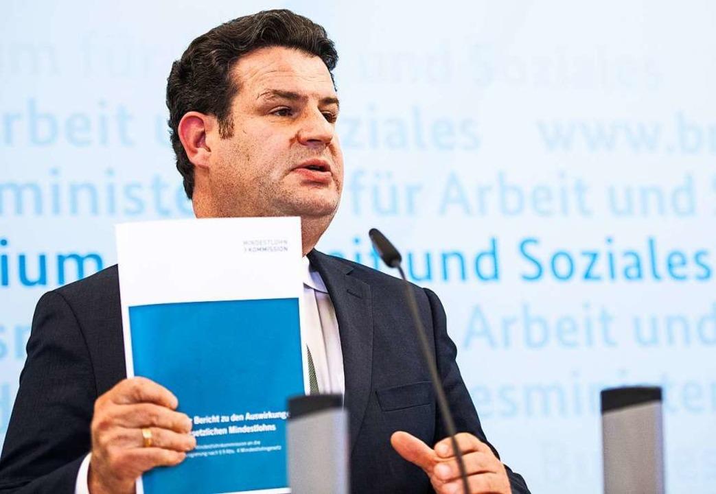 Hubertus Heil (SPD), Bundesminister fü...sion und hält den Bericht in der Hand.  | Foto: Christophe Gateau (dpa)