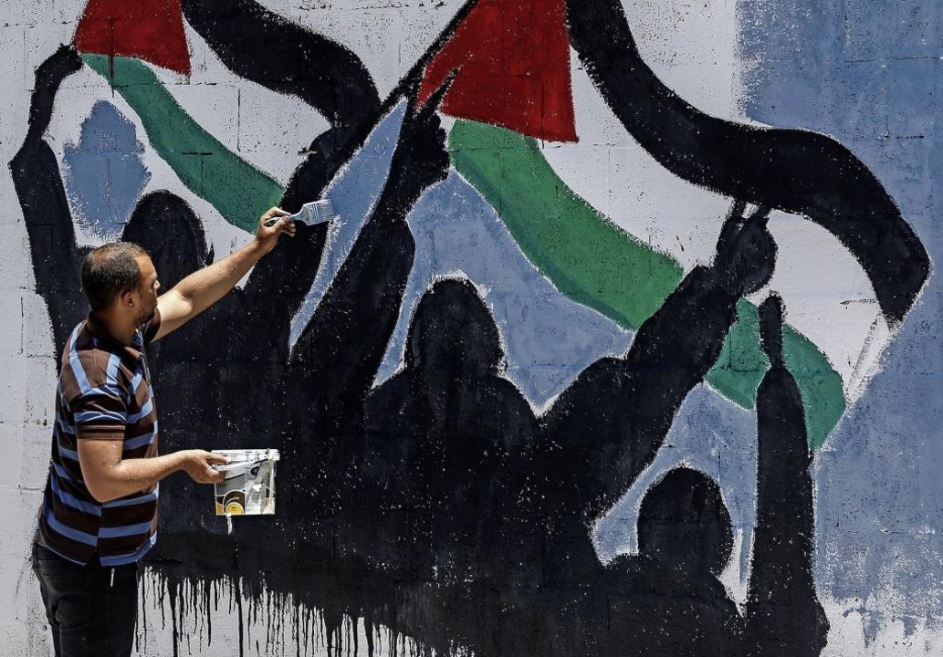Protest mit dem Pinsel: Ein palästinen...inem Mauerbild gegen Netanjahus Pläne.  | Foto: SAID KHATIB (AFP)
