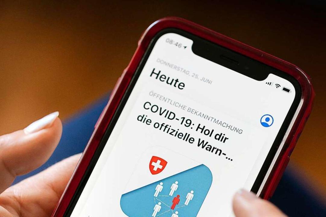 Eine Frau installiert die SwissCovid Contact Tracing App auf ihrem Smartphone.  | Foto: Gaetan Bally (dpa)