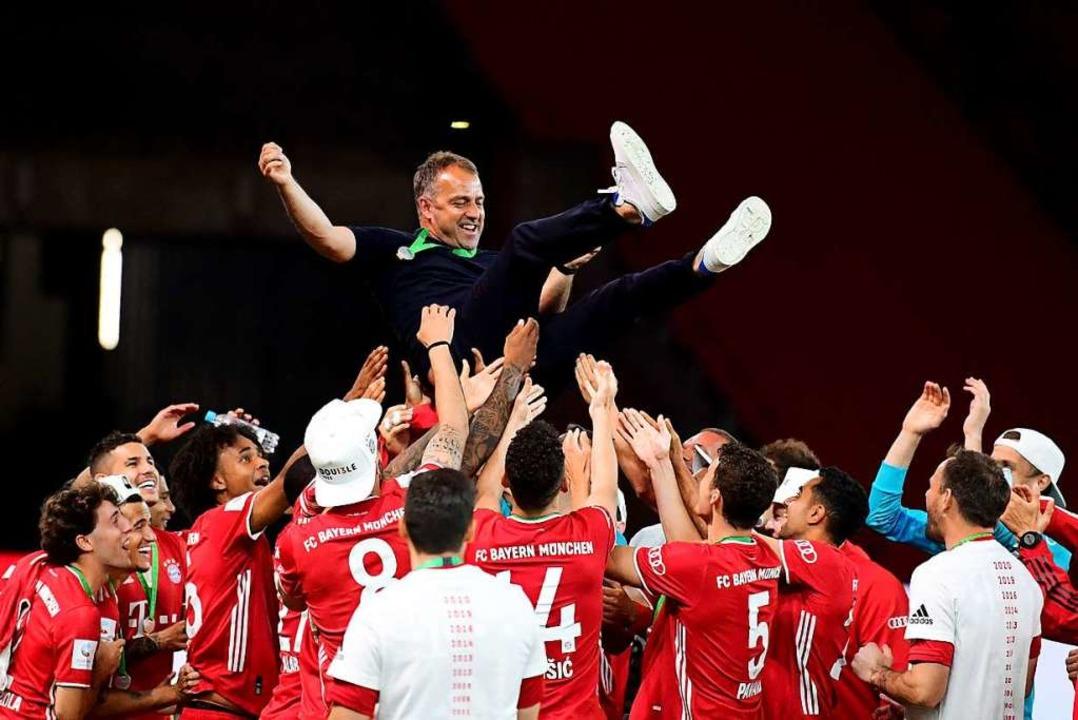 Die Bayern-Spieler feiern ihren Trainer Hans Flick nach dem Pokalerfolg.  | Foto: Robert Michael (dpa)