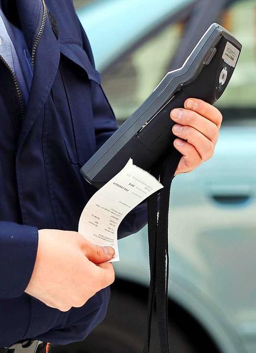 Ein Verkehrspolizist druckt einen Strafzettel aus.    Foto: Roland Holschneider (dpa)