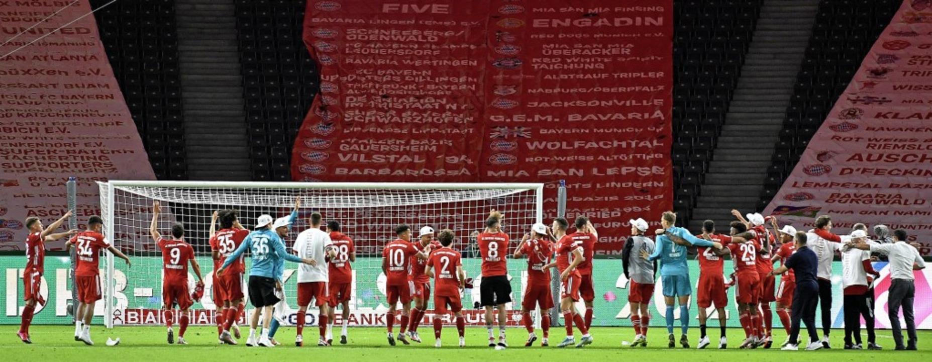 Feiern vor trister Kulisse: Die Bayern...en Rängen im Berliner Olympiastadion.   | Foto: John Macdougall (dpa)