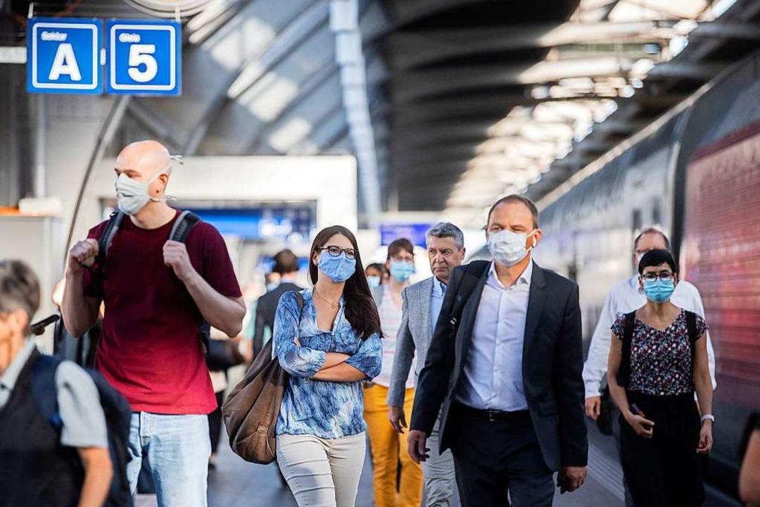 Für die Schweiz ein ungewohntes Bild: ...auptbahnhof mit Mund- und Nasenschutz.  | Foto: Ennio Leanza (dpa)