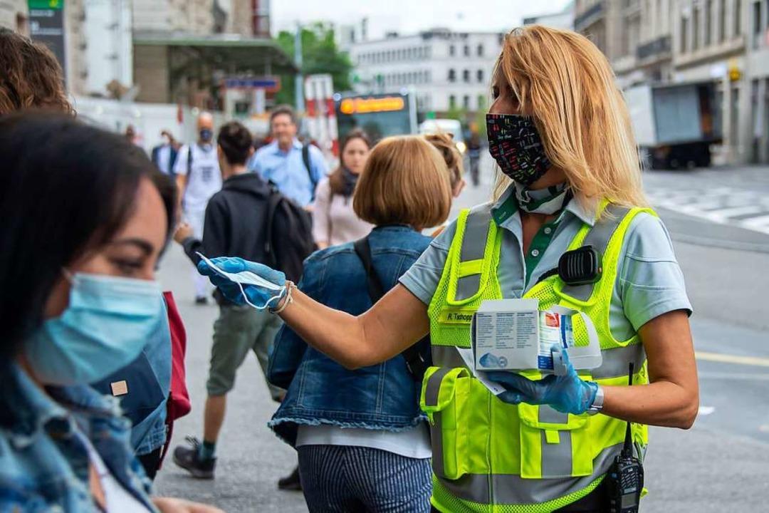 Zum Start verteilten Mitarbeiter der Basler Verkehrs-Betriebe  Schutzmasken.  | Foto: Georgios Kefalas (dpa)
