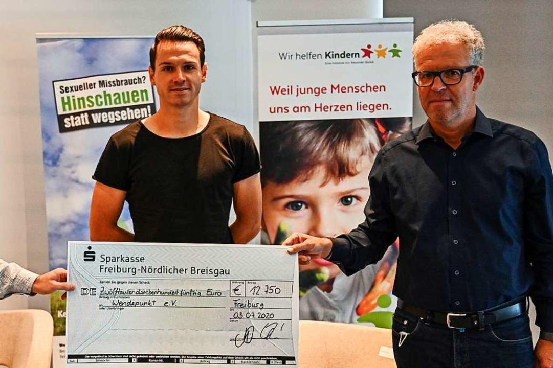 Nicolas Höfler (Mitte) und Hanno Frank...eiburg bei der Übergabe eines Schecks.  | Foto: Achim Keller