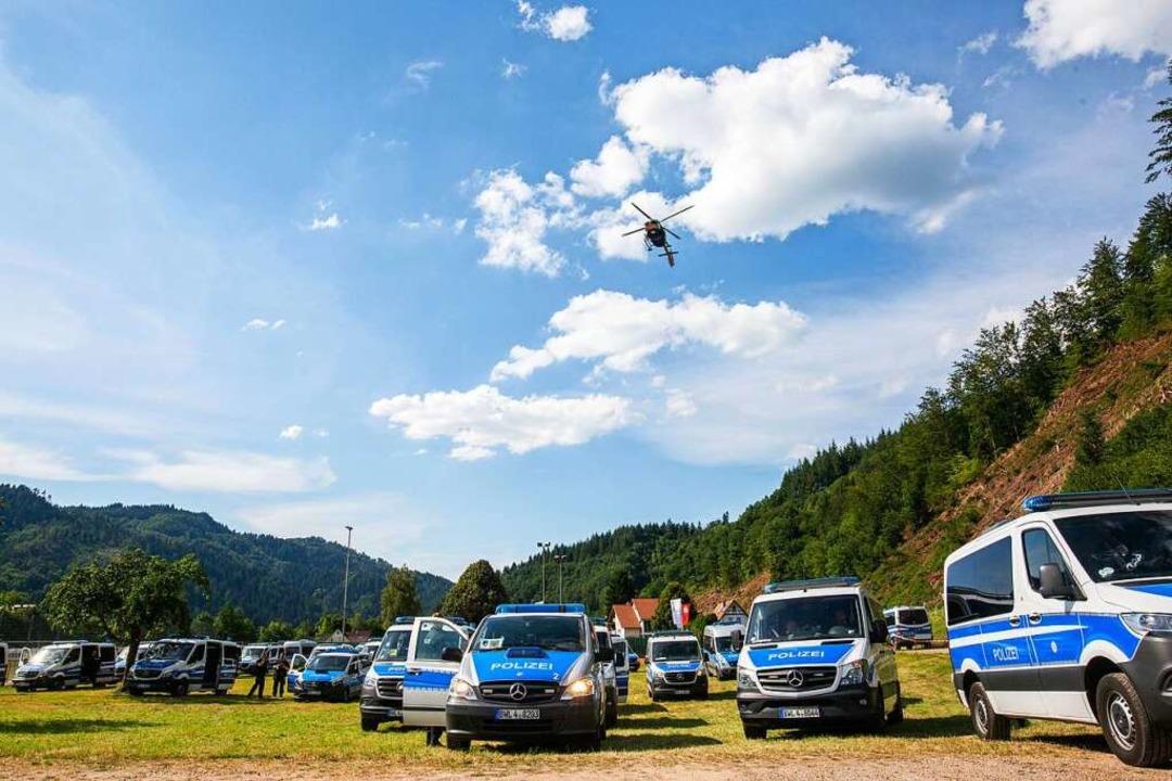 Ein Hubschrauber der Polizei fliegt na...latz, auf dem Polizeifahrzeuge stehen.  | Foto: Philipp von Ditfurth (dpa)