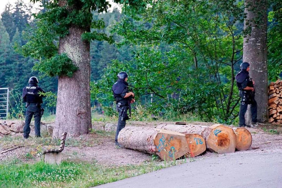 Polizisten durchsuchen ein Waldgebiet.  | Foto: Sven Kohls, SDMG (dpa)