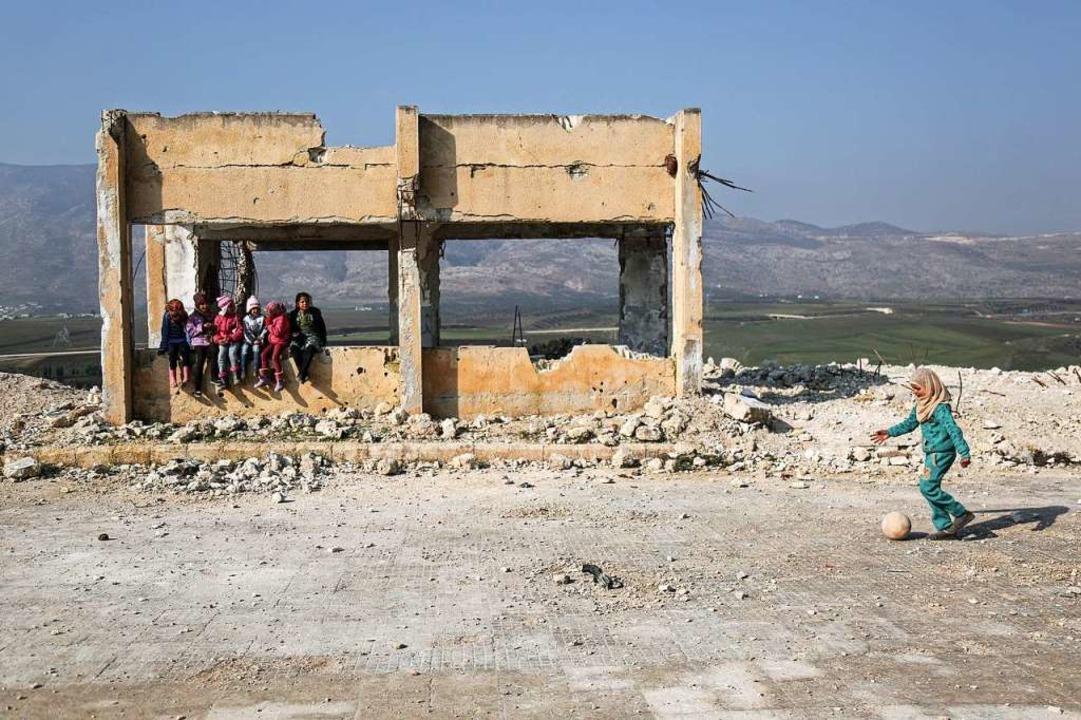 Kinder spielen in den Trümmern einer schwer beschädigten Schule in Syrien.    Foto: Anas Alkharboutli (dpa)
