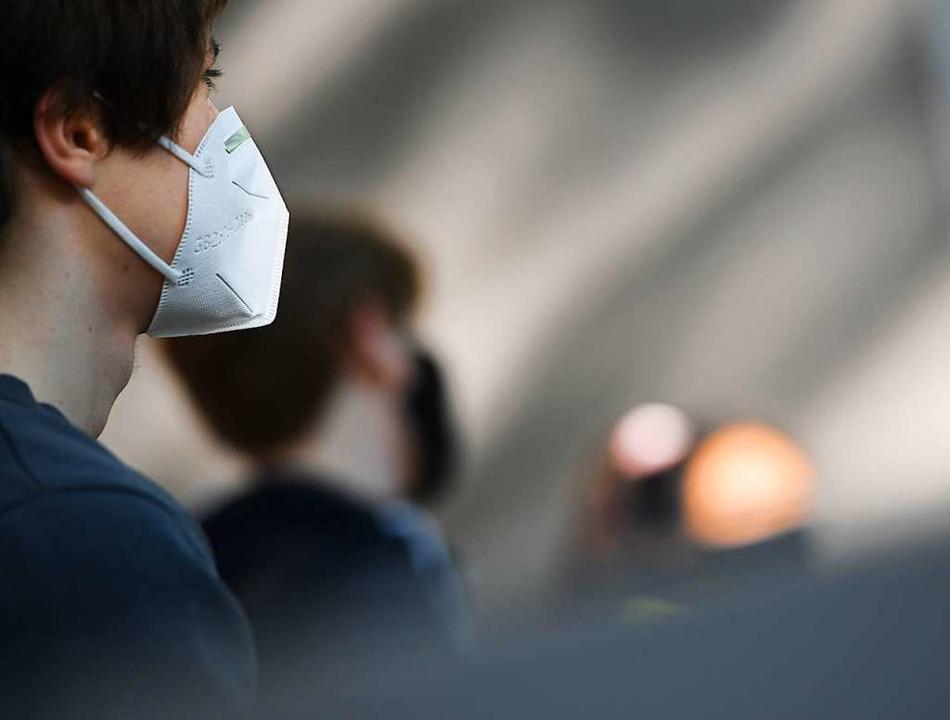 Ein Schüler trägt eine Schutzmaske. Di...n Schulen nach den Ferien wieder Usus.  | Foto: Arne Dedert (dpa)