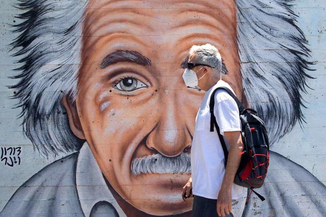 In Tel Aviv in Israel geht ein Mann mi...ild vorbei, das Albert Einstein zeigt.  | Foto: Sebastian Scheiner (dpa)