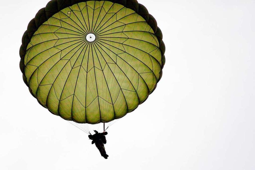 Ein Fallschirmjäger baumelt am Schirm.   | Foto: Bundeswehr/Niklas Pritzsche