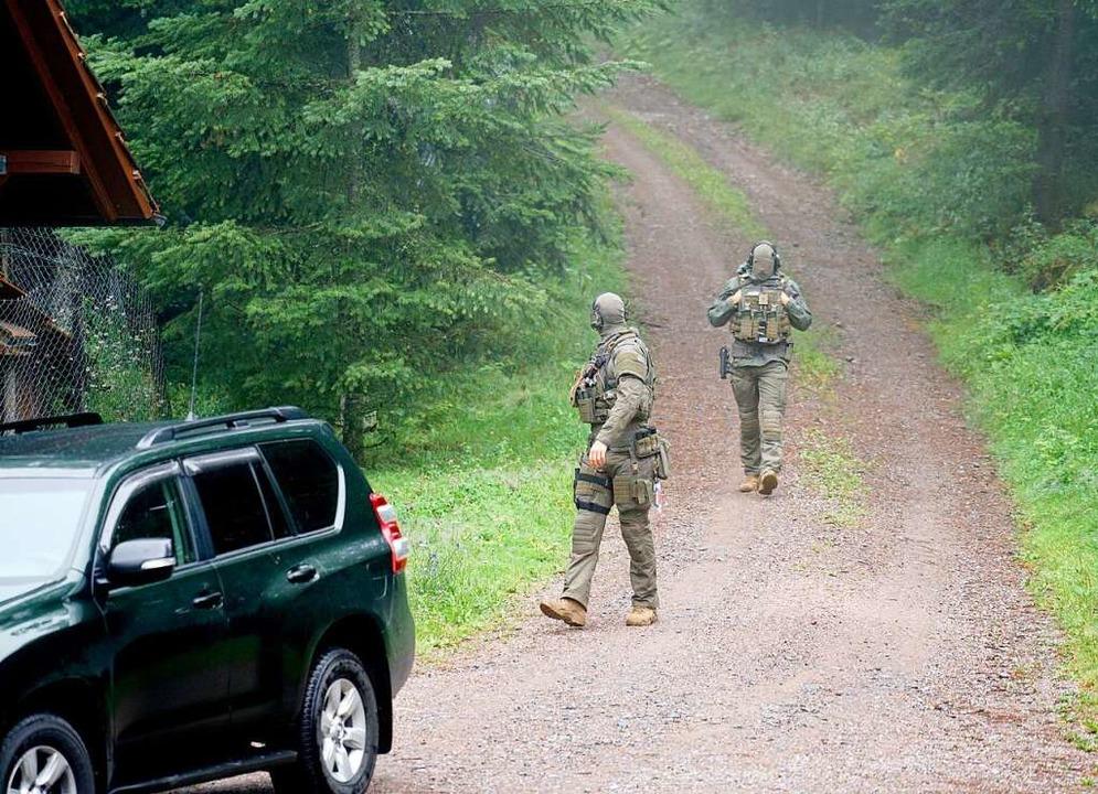 Polizisten am Freitag auf der Suche na...t noch Flüchtigen im Wald von Oppenau.    Foto: Benedikt Spether (dpa)