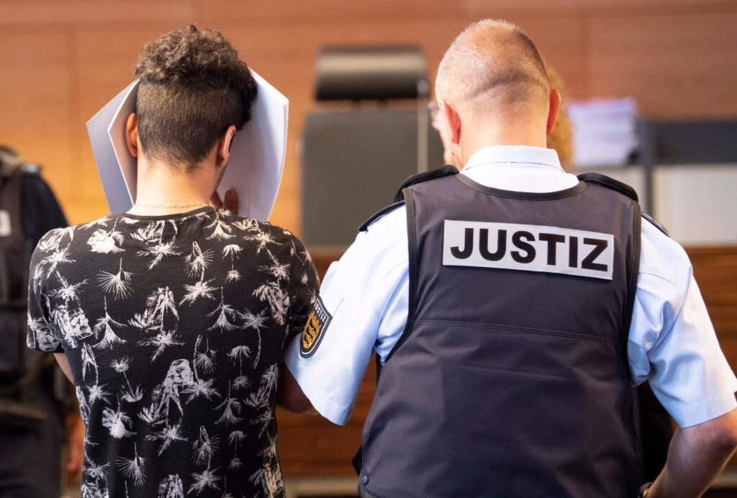 Ein Angeklagter hält eine Mappe als Si...stizbeamter ihn zu seinem Platz führt.  | Foto: THOMAS KIENZLE (AFP)