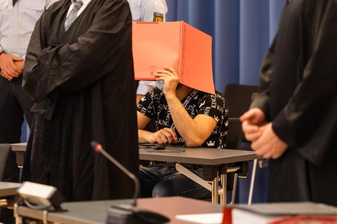 Ein Angeklagter hält eine Mappe als Sichtschutz vor sein Gesicht.  | Foto: Philipp von Ditfurth (dpa)