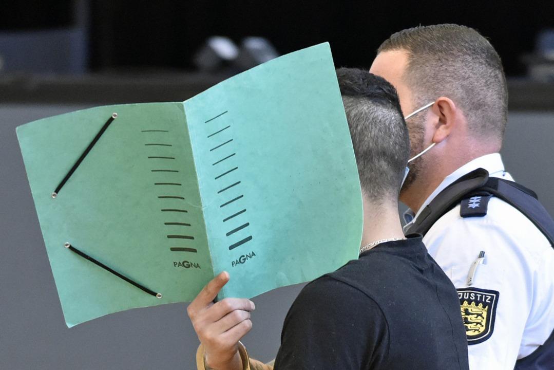 Einer der Angeklagten verdeckt sein Gesicht mit einem Aktenordner.    Foto: Michael Bamberger