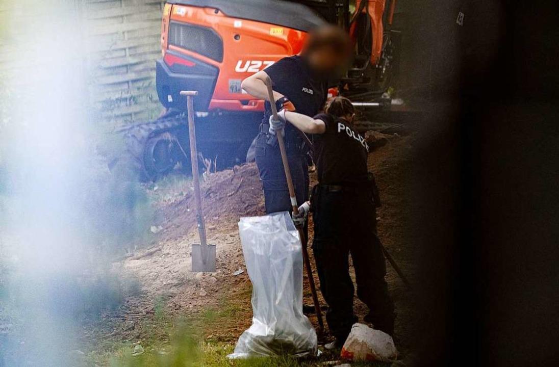 Polizeibeamte durchsuchen eine Kleingarten-Parzelle.  | Foto: Peter Steffen (dpa)