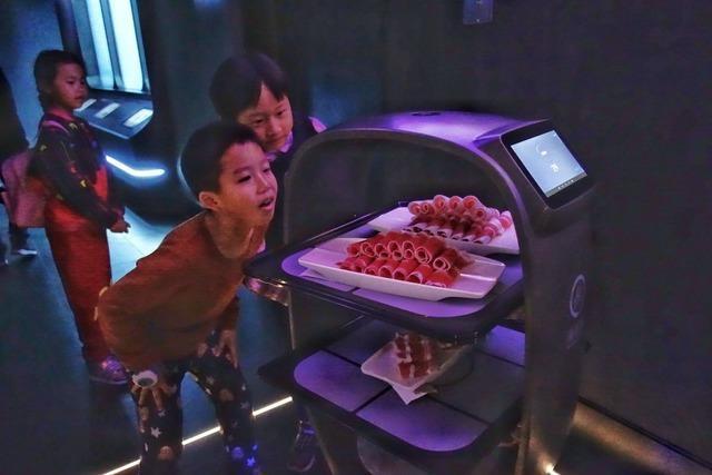 In einem Restaurant in Peking bringen Roboter das Essen