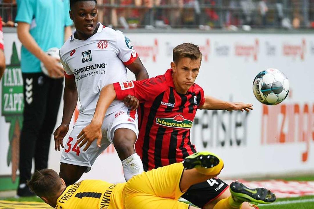 Niko Schlotterbeck kämpft mit Boto Bak...orwart Alexander Schwolow um den Ball.  | Foto: Patrick Seeger (dpa)