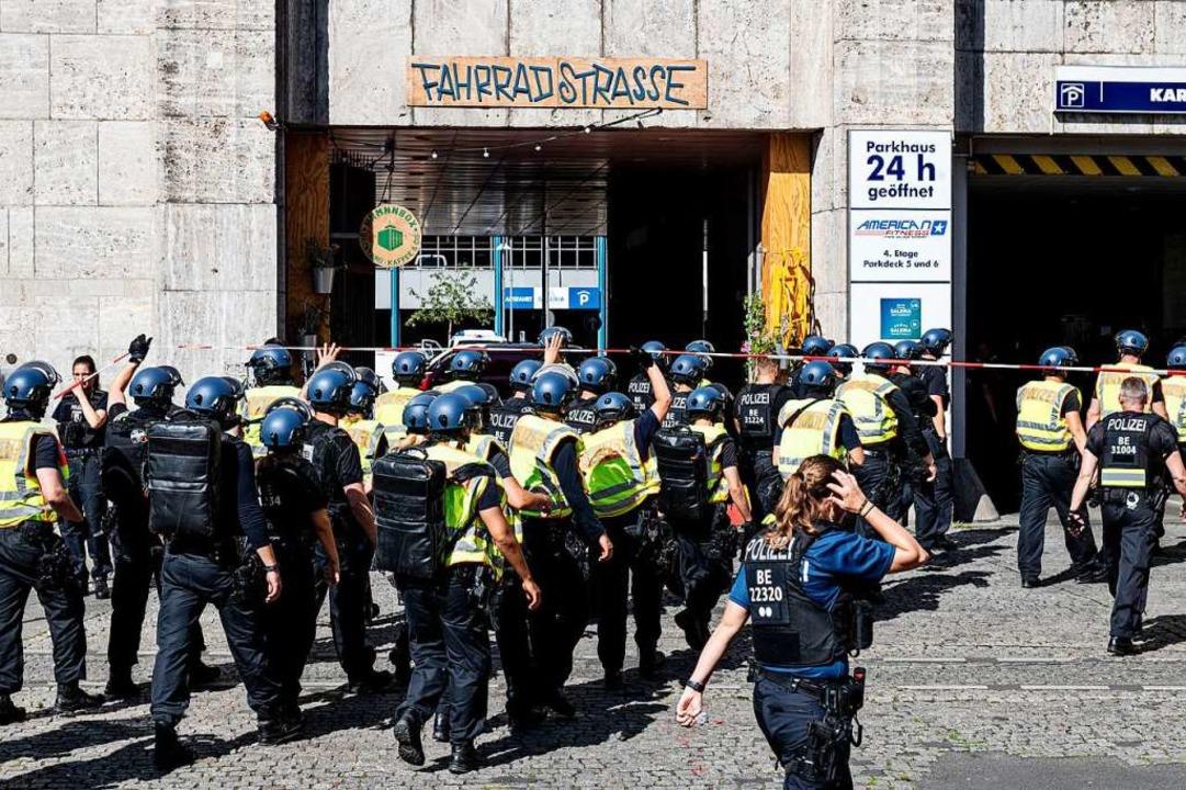 Schwer bewaffnete Polizeibeamte stehen am Hermannplatz in Berlin-Neukölln.    Foto: Fabian Sommer (dpa)