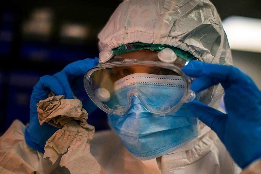 Eine Mitarbeiterin eines Krankenhauses...Barcelona passt ihre Schutzbrillen an.  | Foto: Emilio Morenatti (dpa)