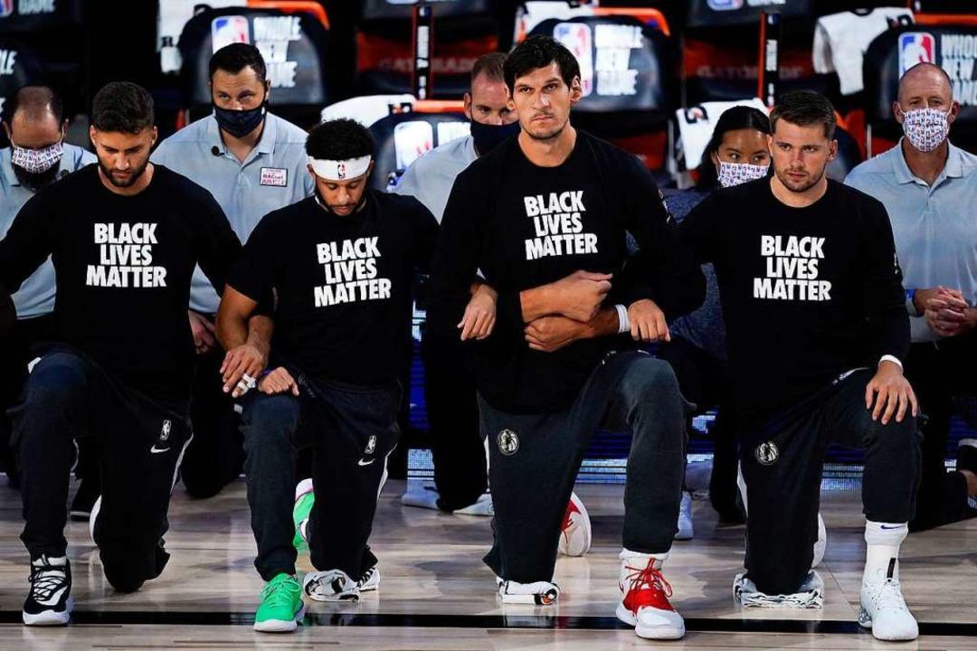 Spieler des Basketballteams Dallas Mav...hrend die Nationalhymne gespielt wird.    Foto: Ashley Landis (dpa)