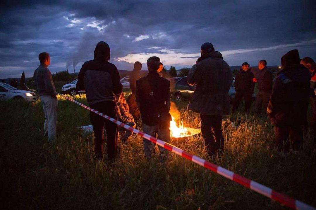 Auf der anderen Seite wärmen sich die Umweltschützer am Lagerfeuer.    Foto: Alna_Morozova