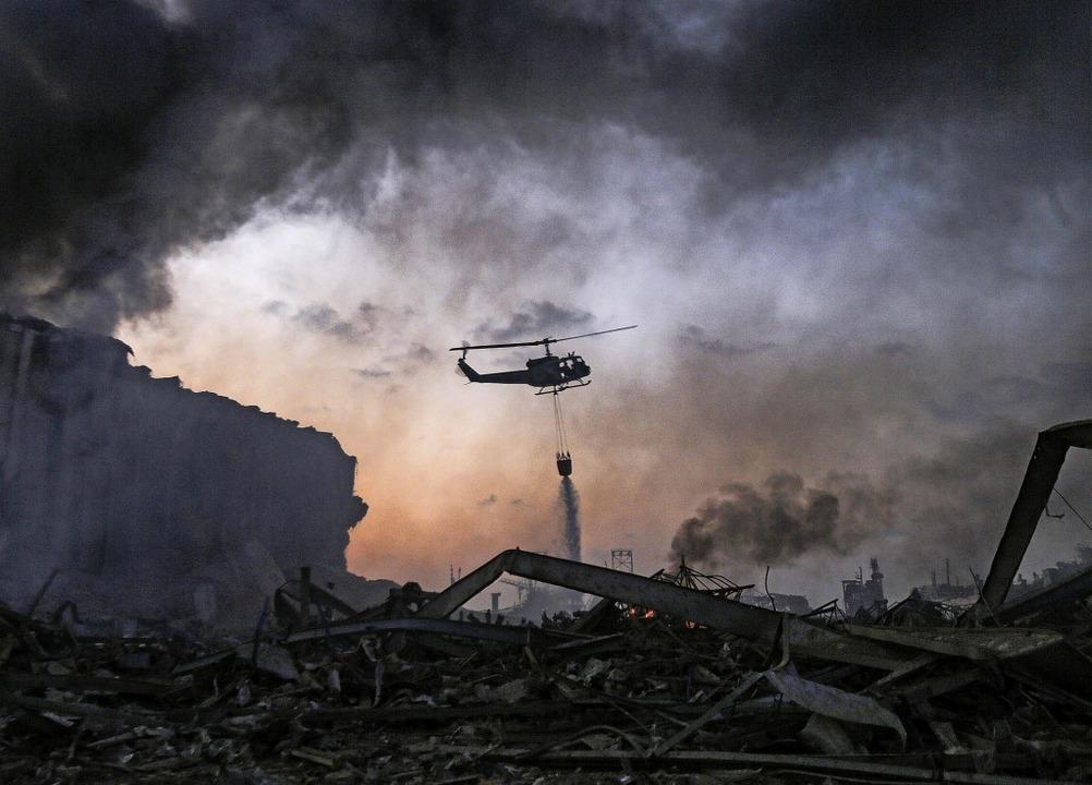 Ein Löschhubschrauber ist über dem Hafen von Beirut im Einsatz.   | Foto: STR (AFP)
