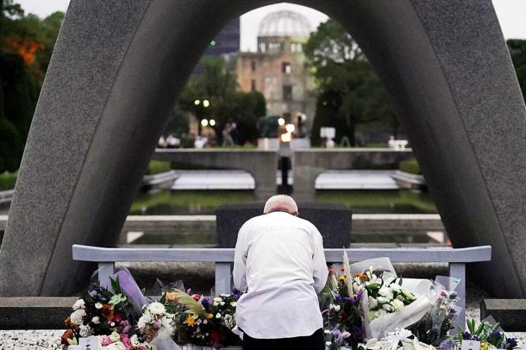Ein Mann betet vor dem Kenotaph für di...be am 75. Jahrestag des Bombenabwurfs.  | Foto: Eugene Hoshiko (dpa)