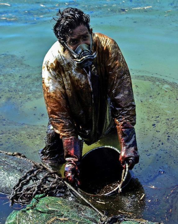 Verzweifelt versuchen Bewohner von Mauritius das Öl aus dem Wasser zu bekommen.   | Foto: JEAN AURELIO PRUDENCE (AFP)