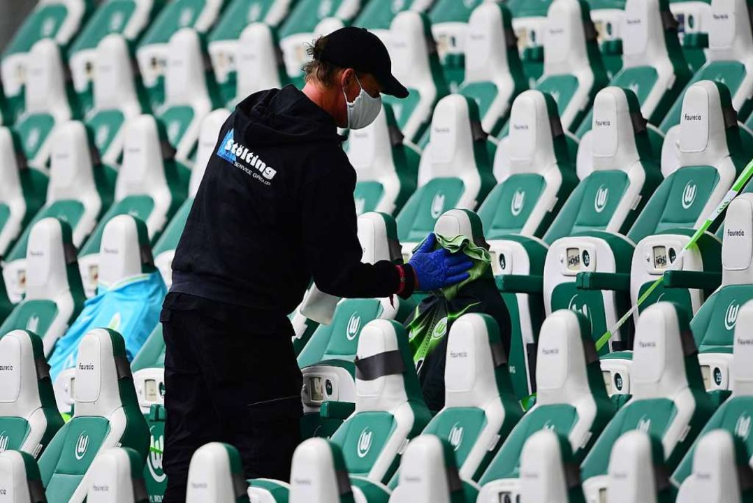 Desinfizieren – aber für wen? Ei...arbeiter im Stadion des  VfL Wolfsburg  | Foto: Swen Pförtner (dpa)
