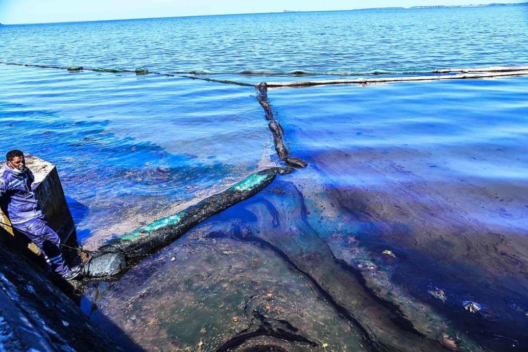 Mit handgefertigten Barrieren versuchen die Menschen, das Öl aufzuhalten.  | Foto: BEEKASH ROOPUN (AFP)