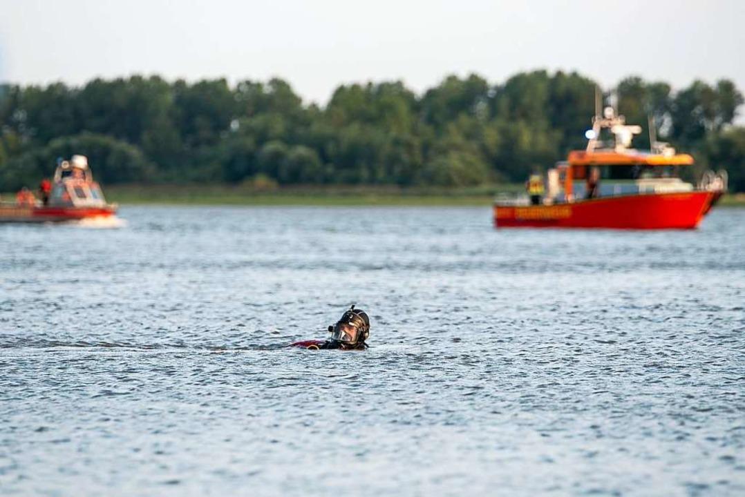 An der Stelle, wo der oder die Vermiss...ehen die Rettungstaucher unter Wasser.  | Foto: Jonas Walzberg (dpa)