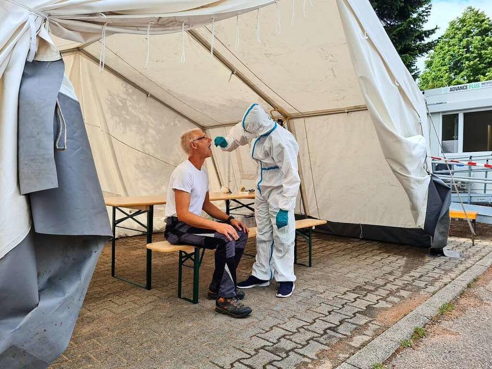 Zwei Helfer demonstrieren in der Abstr...äckingen,  wie ein Coronatest abläuft.  | Foto: Stefan Ammann