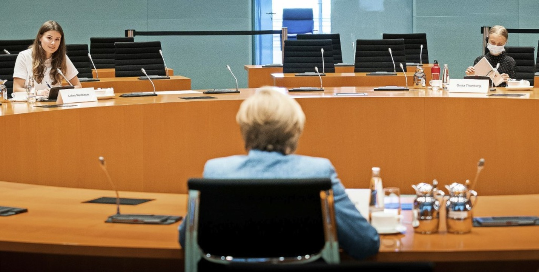 Merkel bespricht sich im Konferenzsaal... (rechts) und Luisa Neubauer (links).     Foto: Steffen Kugler (dpa)